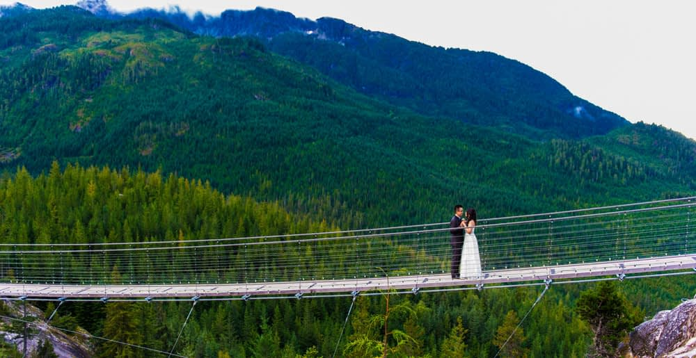 Sea to Sky couple on the bridge with mountains in the back