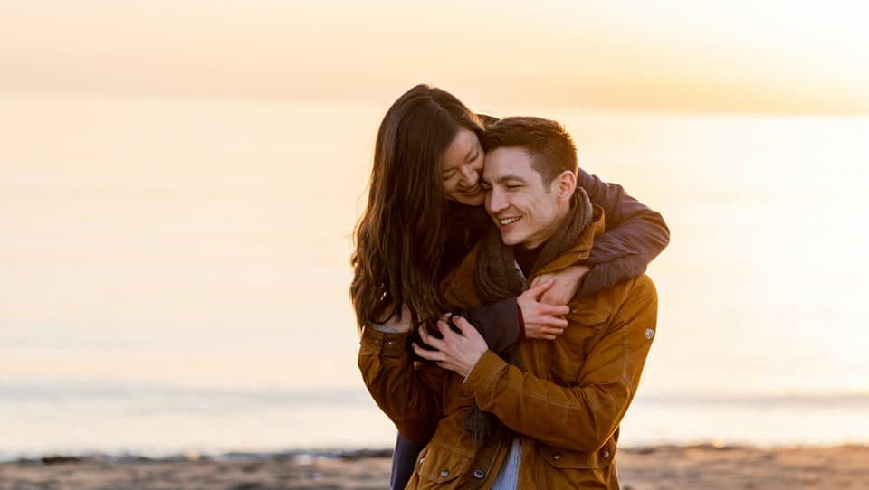 lady hugging her new fiancé at Iona Beach during sunset