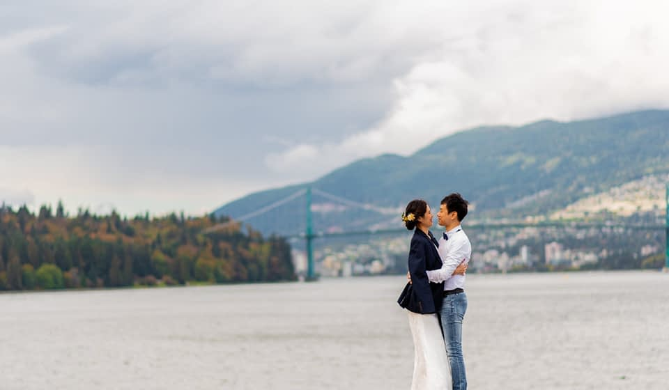 Lions Gate bridge in the background during Stanley Park engagement