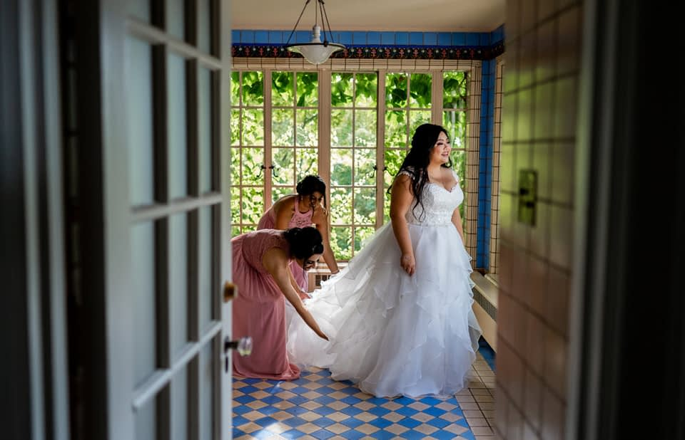 bridesmaid and bride getting ready in the Farris Room at Hycroft Manor