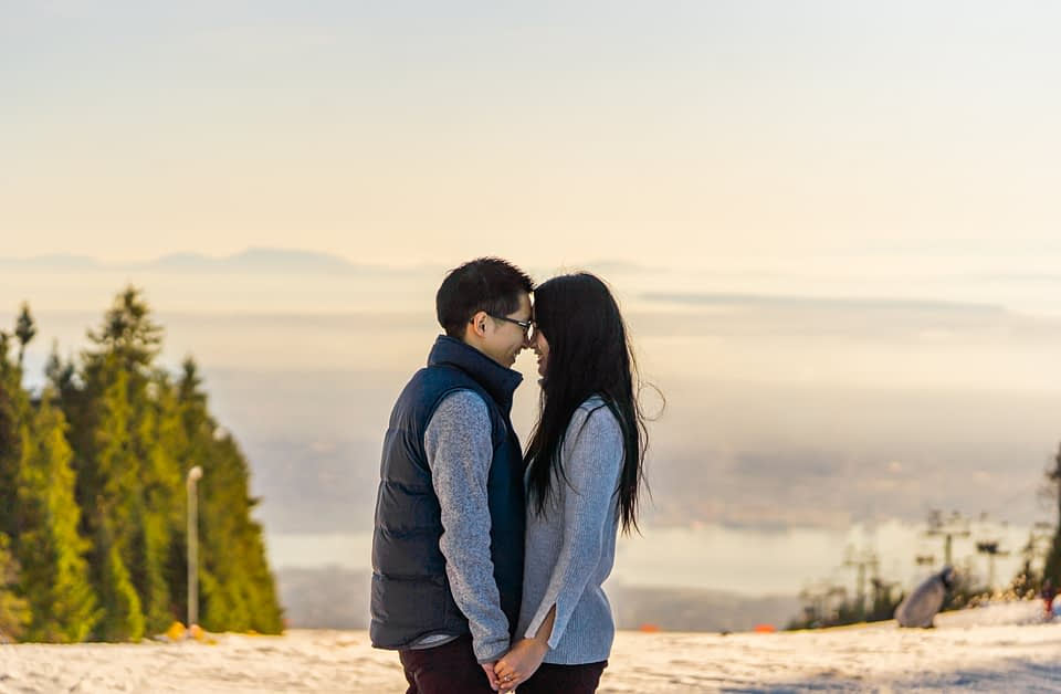 couple holdings hands on the top of Grouse Mountain