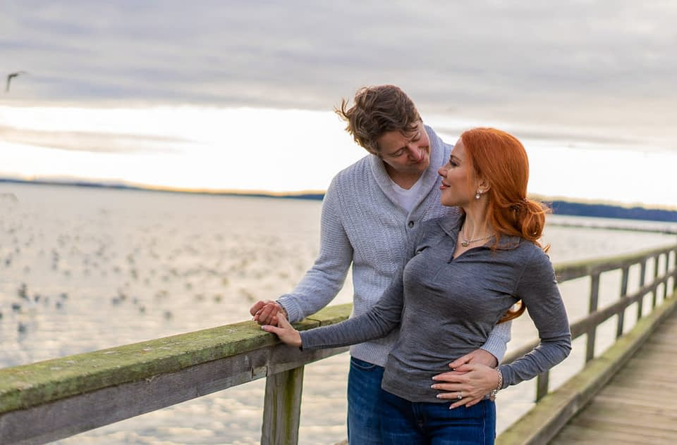 Couple cuddling for their White Rock Pier engagement session