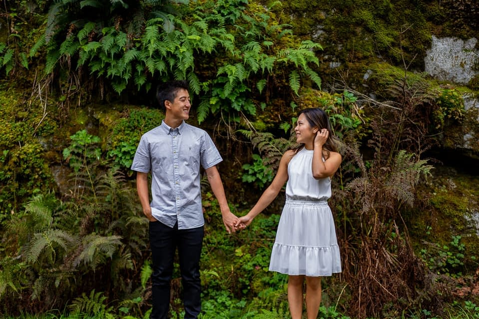 Couple in front of a grass wall for their Othello Tunnels engagement photos