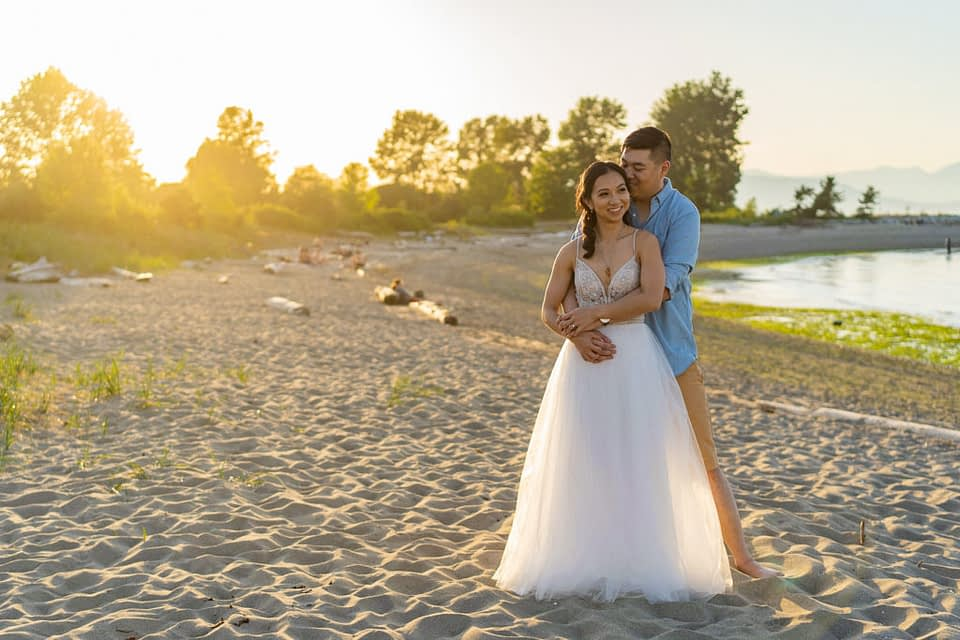 Engaged couple on Jericho Beach with a sunset