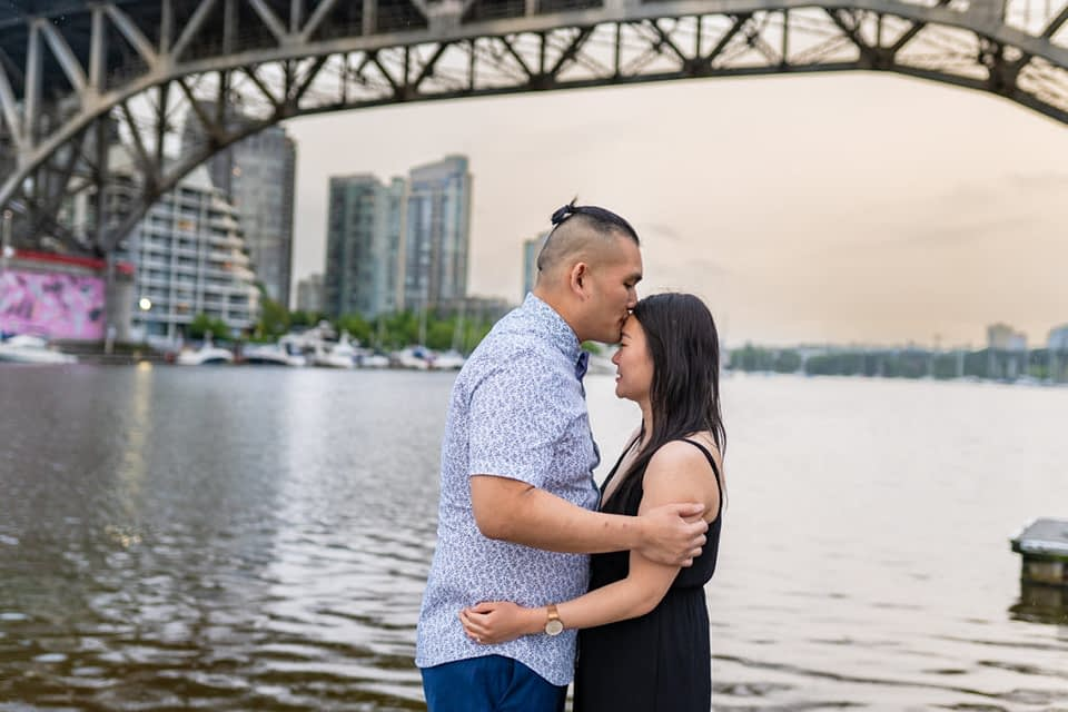 fiancé kissing his partner on the forehead at Granville Island