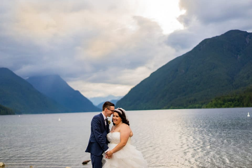 bride and groom walking on the beach at Alouette lake in Golden Ears Provincial Park