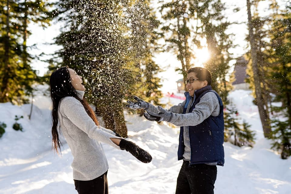 couple throwing snow in the air
