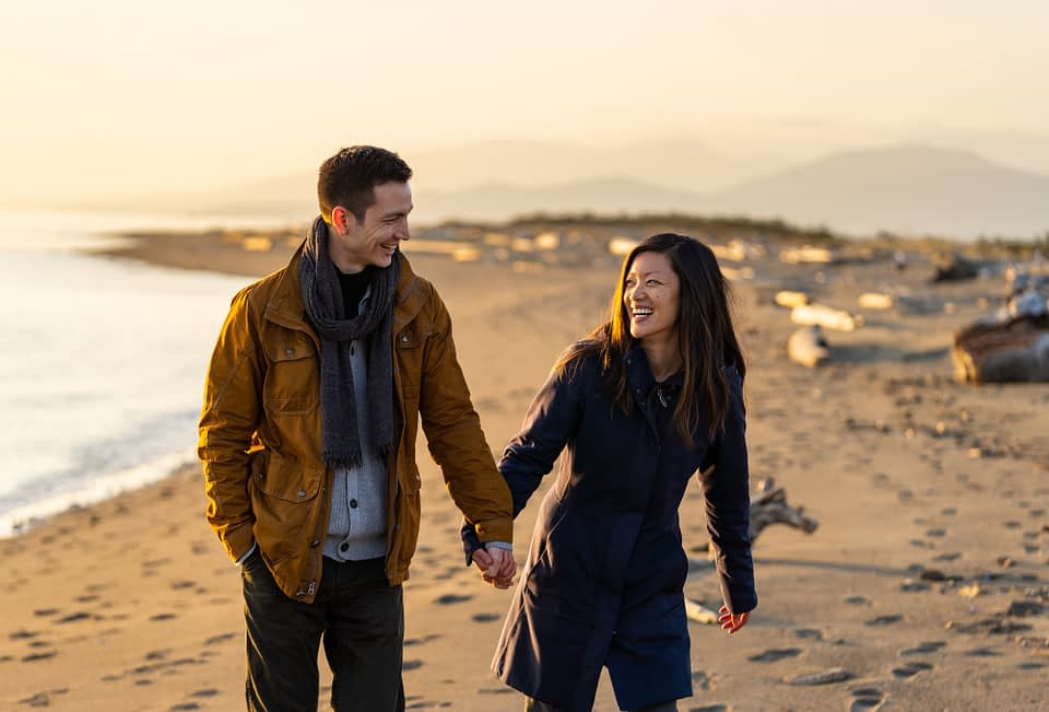 couple walking during sunset at Iona Beach during their engagement session