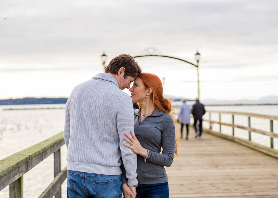 White Rock Pier with a newly engaged couple holding hands for their engagement session